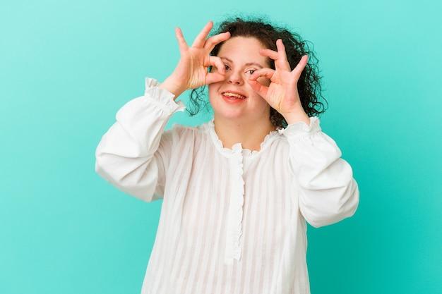 Vrouw met het syndroom van down geïsoleerd ok teken over ogen tonen