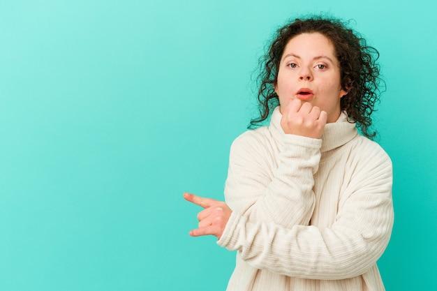 Vrouw met het syndroom van down geïsoleerd wijzend naar de zijkant