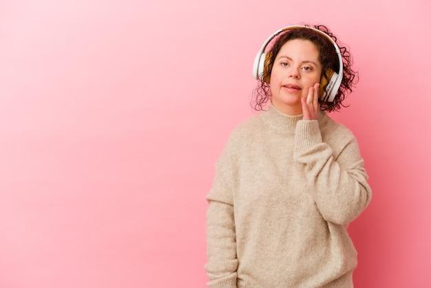 Vrouw met het syndroom van down met koptelefoon geïsoleerd op roze muur zegt een geheim heet remmend nieuws en kijkt opzij
