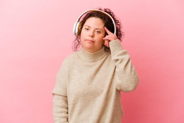 Vrouw met het syndroom van down met koptelefoon op roze met een gebaar van teleurstelling met wijsvinger.