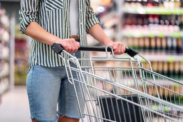 Vrouw met het winkelen karretje in supermarkt. eten kopen in de supermarkt. boodschappen doen