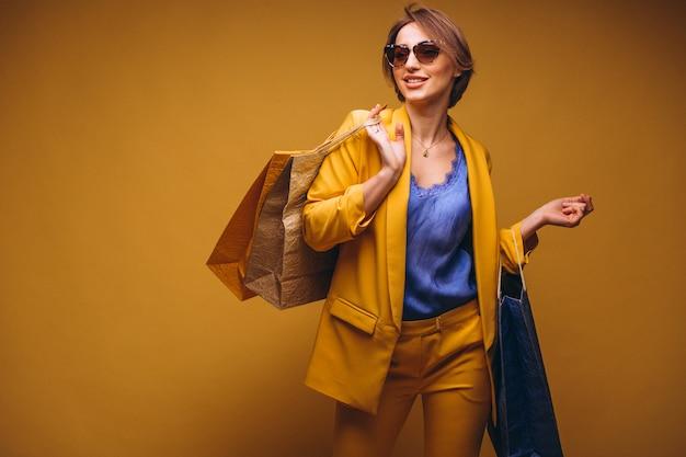 Vrouw met het winkelen zakken in studio op gele geïsoleerde achtergrond