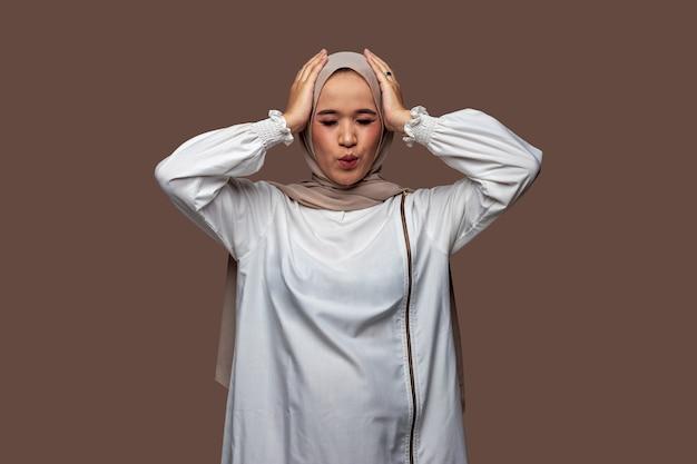 Vrouw met hijab die het hoofd met beide handen vasthoudt terwijl ze haar ogen sluit closing