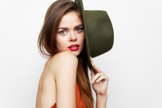Vrouw met hoed bedekt haar gezicht in een rode jurk