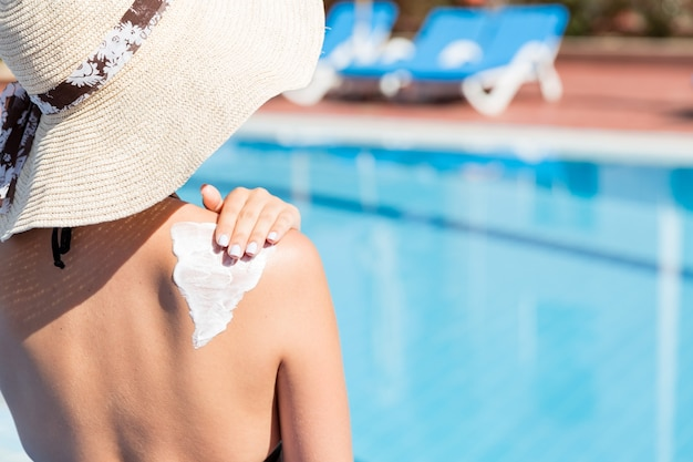 Vrouw met hoed brengt zonnebrandcrème aan op haar schouder bij het zwembad. zonbeschermingsfactor in vakantie, concept.