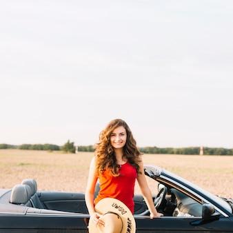 Vrouw met hoed dichtbij auto