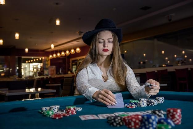 Vrouw met hoed die haar kaarten controleert in casino
