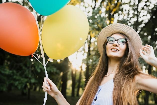Vrouw met hoed en ballonnen in park