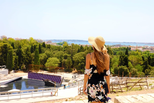 Vrouw met hoed en kleding op de tribunes van het griekse theater van syracuse, sicilië, italië