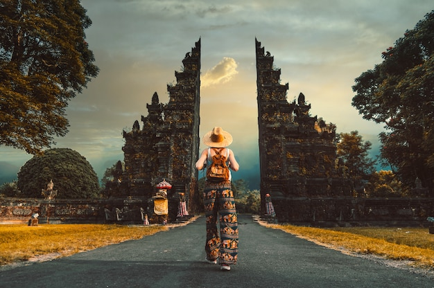 Vrouw met hoed en rugzak die de ingang van de hindoe-tempel in bali, indonesië binnenlopen