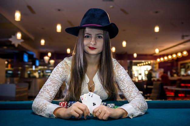 Vrouw met hoed heeft vier azen in casino