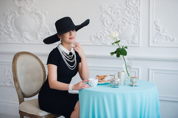 Vrouw met hoed, net als de beroemde actrice, croissant die thee eet en drinkt.