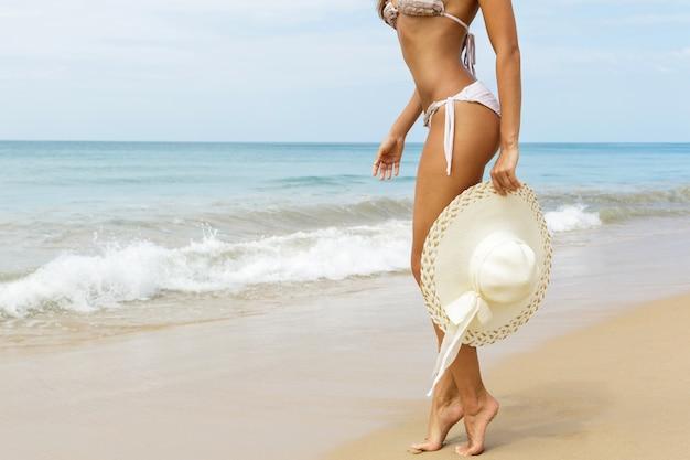 Vrouw met hoed op het strand