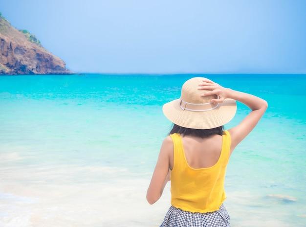 Vrouw met hoed staande op beeld vervagen van op blauwe zee