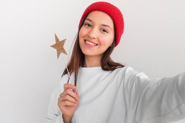 Vrouw met hoed ster decoraties selfie te houden