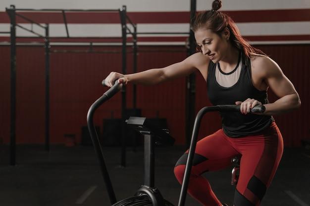 Vrouw met hometrainer in de sportschool. fitness vrouw met behulp van lucht fiets voor cardiotraining bij sportschool.