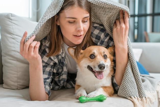 Vrouw met hond onder deken op bank