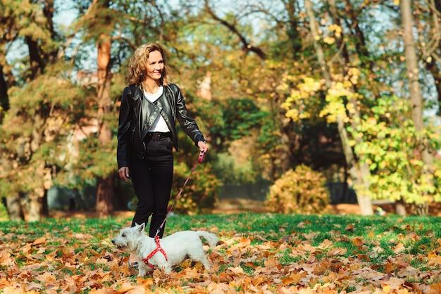 Vrouw met hond wandelen in herfst park. mooie blonde en haar hond tussen gevallen bladeren.