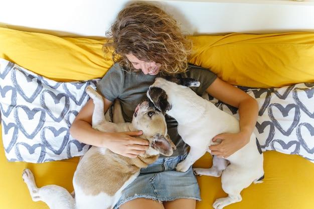 Vrouw met honden in bed. bovenaanzicht van onherkenbare vrouw die een paar franse buldoggen thuis knuffelt.