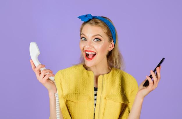 Vrouw met hoofdband houdt handset en smartphone vast stijlvolle vrouw houdt bedrade telefoon en mobiele telefoons vast