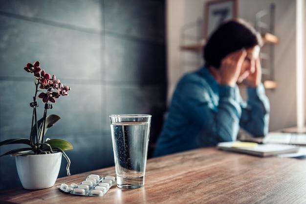 Vrouw met hoofdpijn en capsules met glas water op een bureau