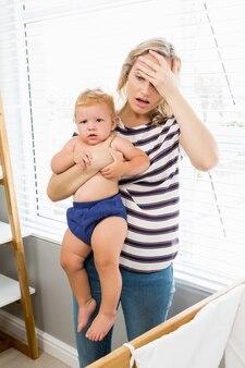 Vrouw met hoofdpijn en een baby in de armen