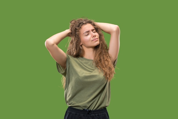 Vrouw met hoofdpijn geïsoleerd over groene muur.