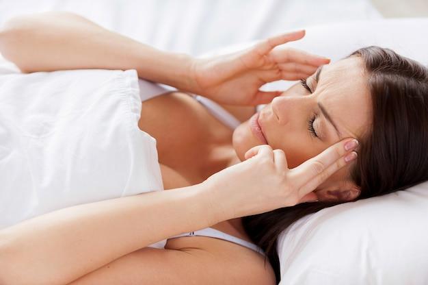 Vrouw met hoofdpijn. knappe jonge shirtloze man die hand in het haar houdt en ogen dicht houdt terwijl hij in bed ligt