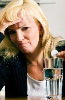 Vrouw met hoofdpijn op het punt om een pil te hebben