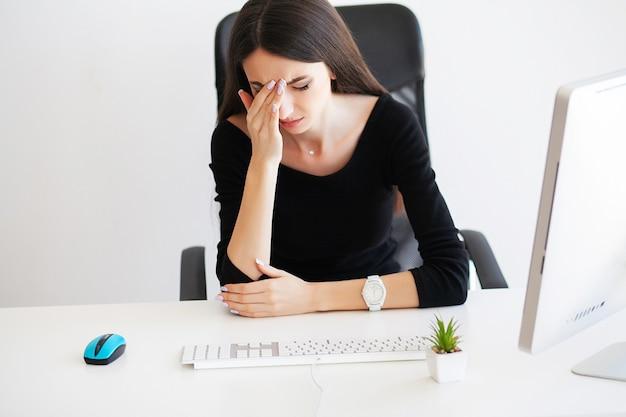 Vrouw met hoofdpijn zitten aan de tafel in het kantoor