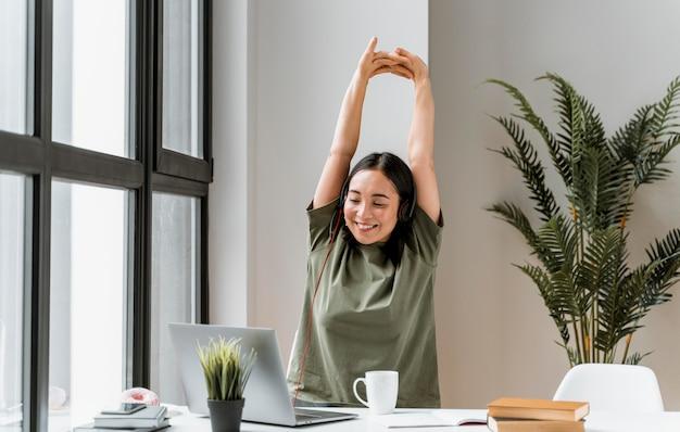 Vrouw met hoofdtelefoon die videogesprek op laptop heeft