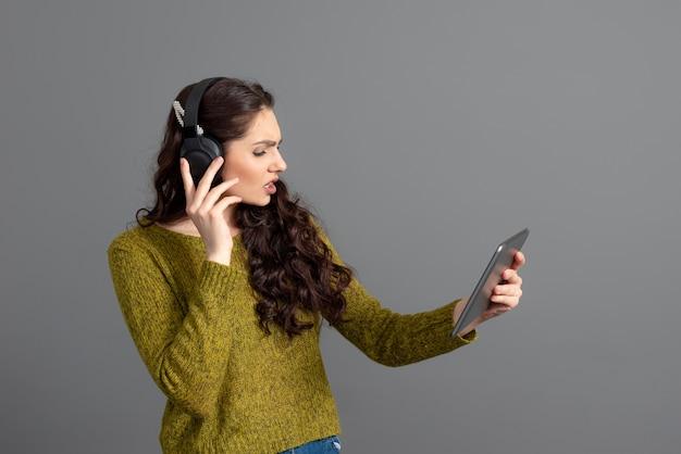 Vrouw met hoofdtelefoon en tablet in hand spelen en online met vrienden praten