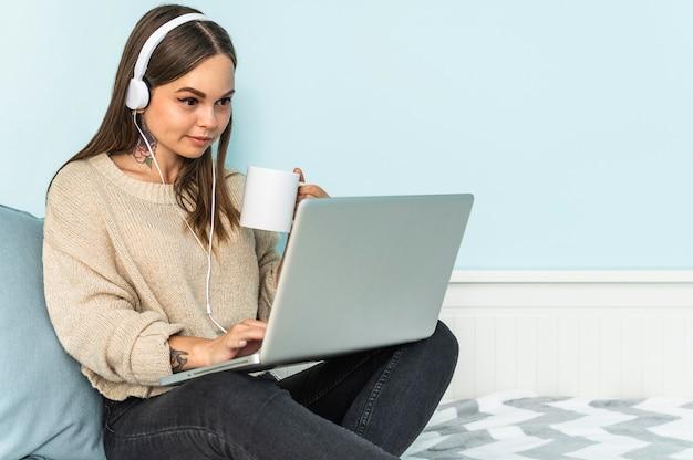 Vrouw met hoofdtelefoons die laptop met behulp van en thuis koffie hebben tijdens de pandemie