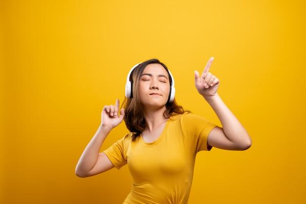 Vrouw met hoofdtelefoons het luisteren muziek op geïsoleerde gele achtergrond