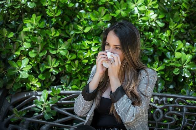 Vrouw met hooikoorts niest in weefsel