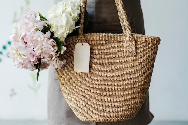 Vrouw met hortensia's in een rieten tas