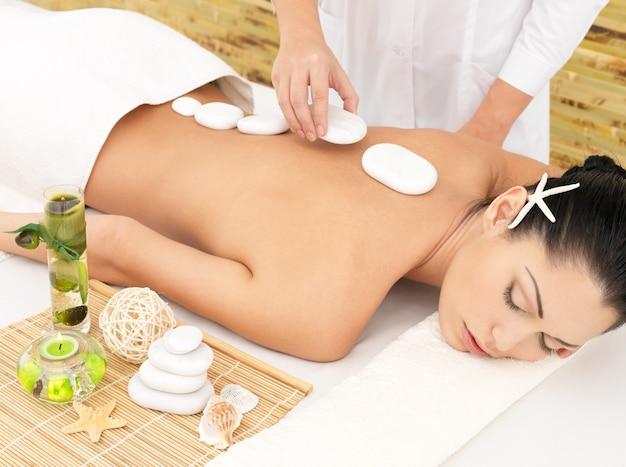 Vrouw met hot stone spa massage van rug in de schoonheidssalon