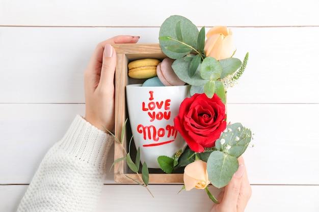 Vrouw met houten kist met geschenken voor moederdag op houten