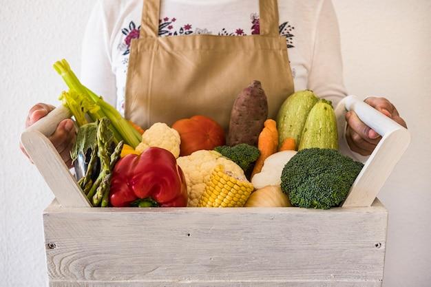 Vrouw met houten kist vol verse rauwe groenten. mand met assortiment van wortelen, bloemkool, courgette, broccoli, maïs, tomaten en paprika - gezond levensstijlconcept