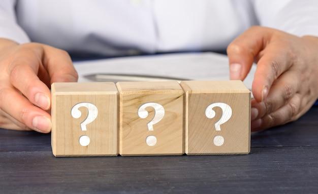 Vrouw met houten kubussen met vraagtekens. vraag en antwoord concept, spanning, close-up