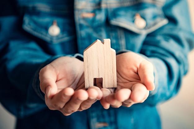 Vrouw met houten modelhuis in haar handen