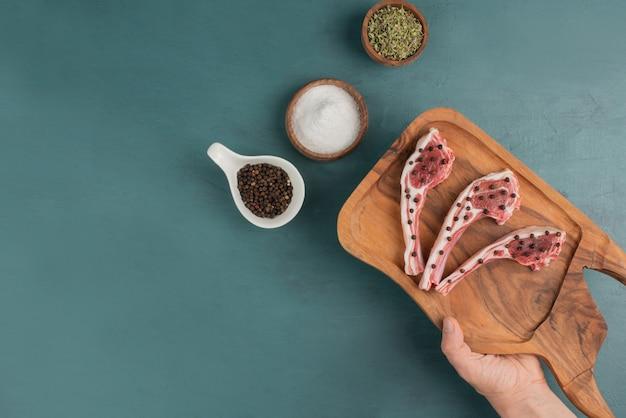 Vrouw met houten plank van rauw vlees stukken.