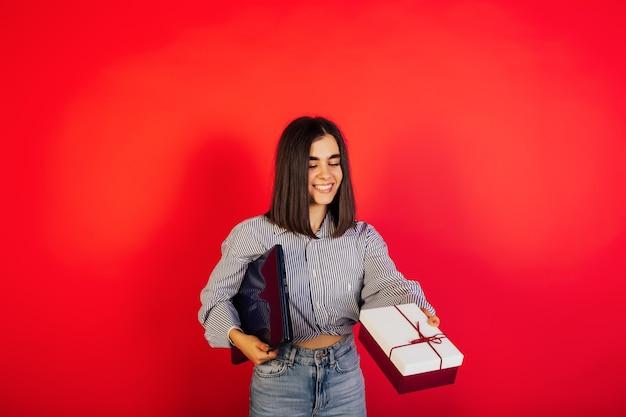 Vrouw met huidige doos en laptop op de rode muur