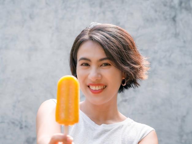Vrouw met ijslolly's. fijne mooie aziatische vrouw met kort haar met een casual wit mouwloos shirt met een gele ijslolly op een grijze betonnen muurachtergrond, zomers.