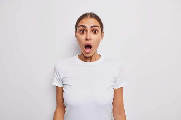 Vrouw met ingehouden adem houdt mond wijd open kan haar ogen niet geloven gekleed in een casual t-shirt op wit