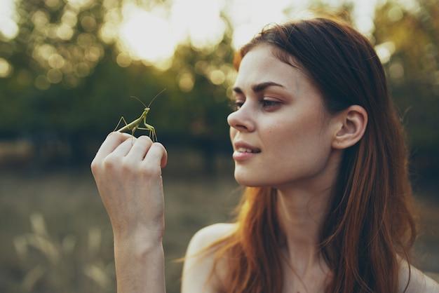 Vrouw met insect op haar hand bidsprinkhaan natuur bomen zomer.