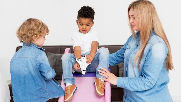 Vrouw met jongens die bij de dia spelen