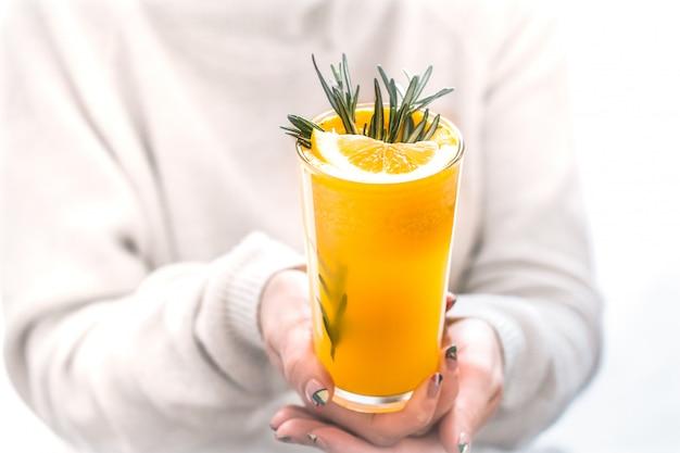 Vrouw met jus d'orange met rozemarijn