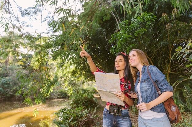 Vrouw met kaart die plaats toont aan haar vrouwelijke vriend in bos