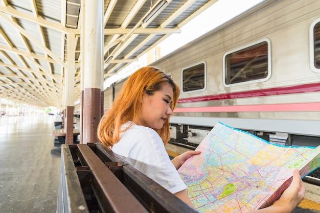 Vrouw met kaart op zetel dichtbij trein op platform